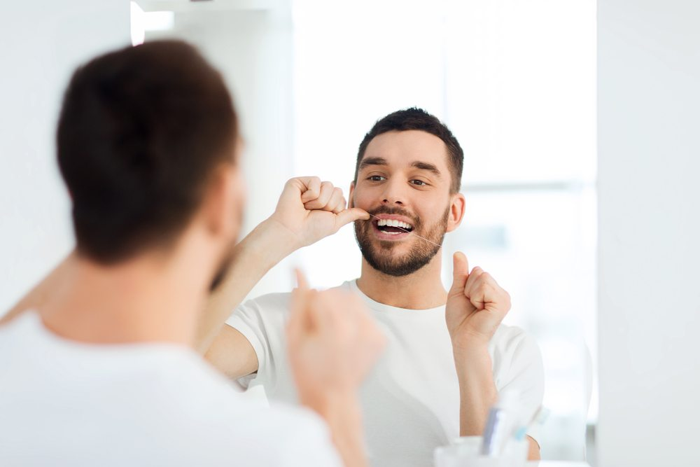 Smiling young man looking to mirror and cleaning teeths