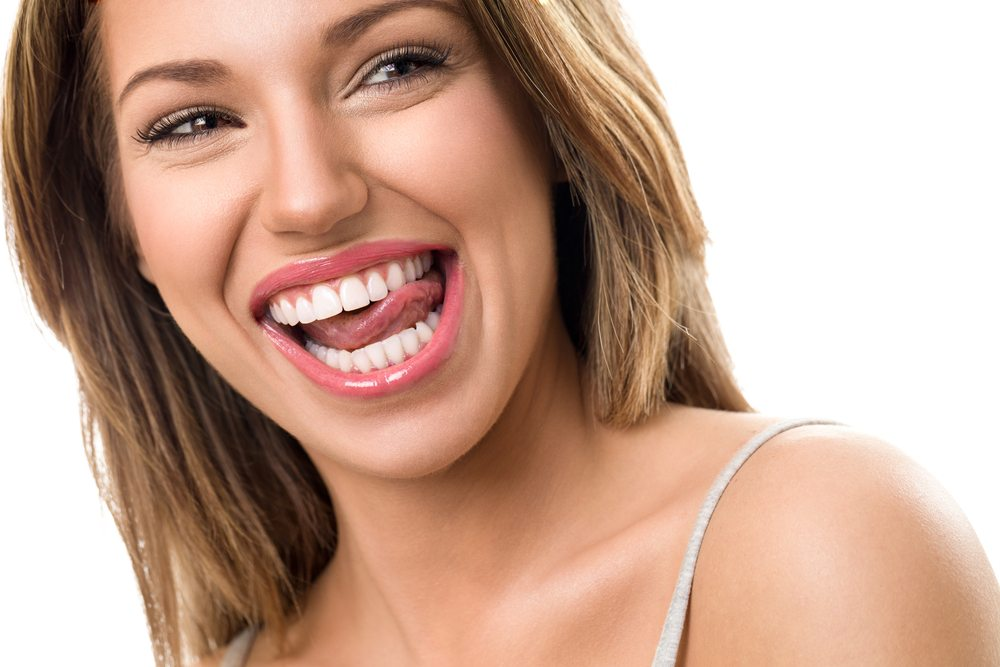Beautiful young woman biting tongue with perfect teeth